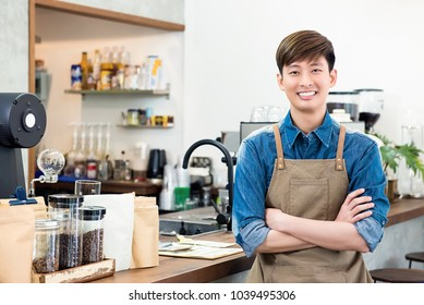 Cheerful young Asian man entrepreneur standing at counter in his own coffee shop