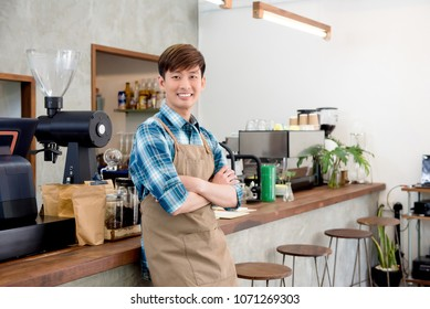Cheerful young Asian man entrepreneur standing with arm crossed at counter in his own coffee shop