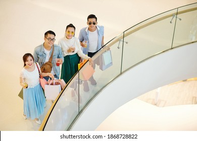 Cheerful young Asian people standing on balcony of shopping mall and looking up at camera