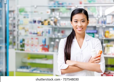 cheerful young asian pharmacist with medication smiling at camera in drugstore