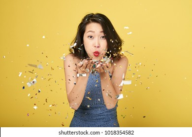 Cheerful young Asian woman blowing confetti into camera