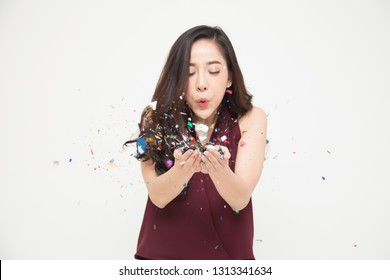 Cheerful young Asian woman blowing confetti into forward on white background