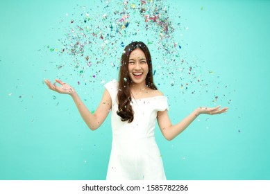 Cheerful young Asian woman celebrating with colorful confetti isolated on green background, Thai model