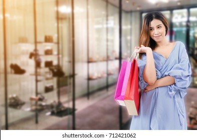 cheerful young asian woman holding shopping bags while standing at trendy shoes shop in department store shopping mall, online payment, shopping online, lifestyle technology concept
