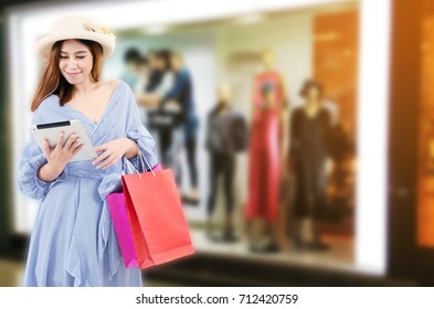 cheerful young asian woman watching special offer in mobile tablet and holding shopping bags while standing at clothes shop in department store shopping mall, online payment, shopping online concept