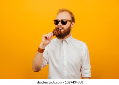 Cheerful young bearded hipster man eating a bar of chocolate over orange background. Unhealthy concept.
