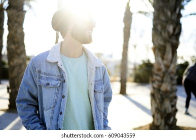 Cheerful young bearded male tourist having city tour enjoying sunny weather on weekends dressed in trendy streetwear with copy space area for brand name standing outdoors on promotional background