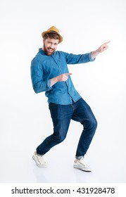 Cheerful young bearded man dancing isolated on the white background