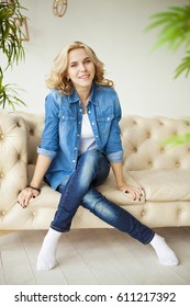 Cheerful young beautiful blonde girl in jeans shirt relaxing and sitting on the couch at home and looking on the camera. Relax at home. Have a fun.