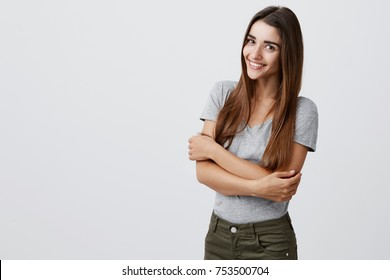 Cheerful young beautiful brunette caucasian student girl with long hair in casual outfit smiling brightly, holding hands together, posing for university graduation photo in light studio. Copy space