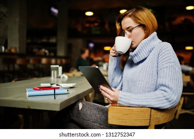 Cheerful young beautiful redhaired woman in glasses using her phone, touchpad and notebook while sitting at her working place on cafe with cup of coffee.