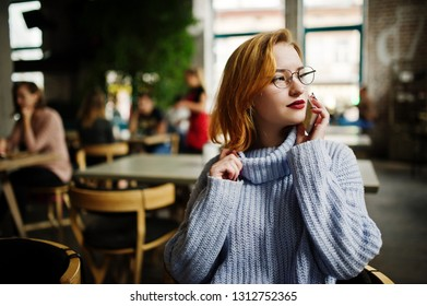 Cheerful young beautiful redhaired woman in glasses sitting at her working place on cafe and speaking by cellphone.