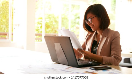 Cheerful young beautiful woman in glasses has online meeting with international business partners, she is sitting at the table at workstation. She is smile while sitting at her working place.