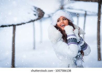 Cheerful young beautiful woman in winter. Female model in snow wearing white jacket and fur hat