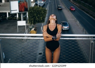 A cheerful young biracial female is leaning against a metal fence