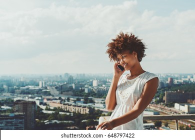 Cheerful young black model girl in simple dress is speaking via smartphone with her agent while standing on balcony of skyscraper high floor with cityscape behind and copy space for text or your logo