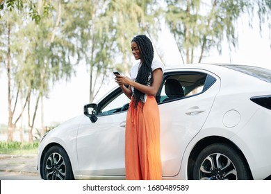 Cheerful young Black woman with long hair standing next to her car and sending text messages to friends
