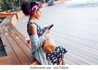 Cheerful young  black woman with stylish Afro hairstyle chatting by mobile phone and sitting in city park. Autumn mood. Wearing grey knitted cardigan and trendy bamboo bag.
