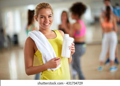Cheerful young blond girl at gym after training with towel and bottle of beverage