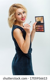 cheerful young blond woman in a dark blue dress is looking at the camera on a white background. Makeup artist holds brushes near the face. Beauty Woman with Makeup Brushes. Natural Make-up for Blonde