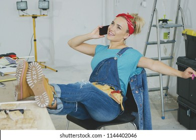 Cheerful young blond woman in jeans overalls and tool belt sitting comfortably with legs on carpenter desk talking on mobile phone with stretched out hand and looking up smiling.