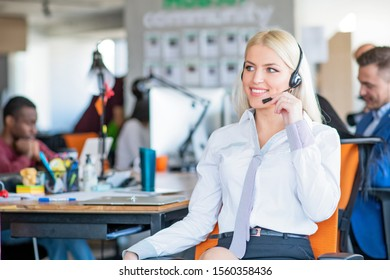 Cheerful young blonde customer service operator at call center