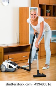 Cheerful young blonde housewife in jeans vacuuming floor and furniture