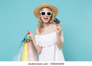 Cheerful young blonde woman in white summer dress hat eyeglasses standing hold package bag with purchases after shopping credit bank card isolated on blue turquoise colour background studio portrait
