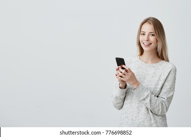 Cheerful young blonde-haired female student with cute smile posing indoors, using cell phone, checking newsfeed on her social network accounts. Pretty girl surfing internet on mobile