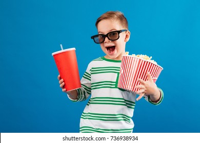 Cheerful young boy in eyeglasses preparing to watch the film while holding soda and popcorn over blue background