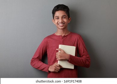 Cheerful young boy holding books in his hands