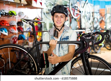 Cheerful young boy looking for and trying new racing bicycle in sport shop