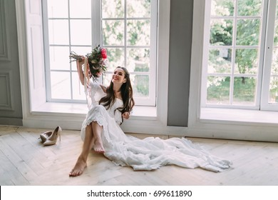 Cheerful, young bride holds a rustic wedding bouquet with white roses and crimson peonies on panoramic window background. Close-up portrait. A happy girl with a bunch of flowers., indoor