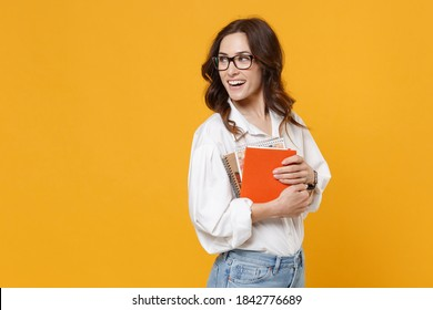 Cheerful young brunette business woman in white shirt glasses isolated on yellow wall background studio. Achievement career wealth business concept. Mock up copy space. Hold notebooks, looking aside