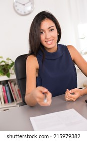 cheerful young brunette business woman holding a pen to customer and inviting to sign a contract
