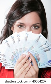 Cheerful young brunette lady holding cash and smilingt