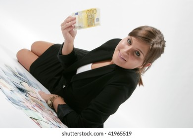 Cheerful young brunette lady holding cash and smiling.