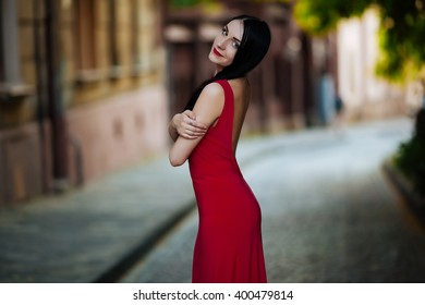 Cheerful young brunette in a red dress posing on the street in Lviv