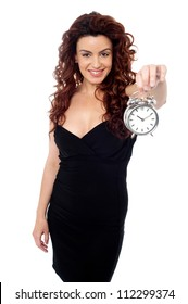 Cheerful young brunette wearing a black dress holding a timepiece in her stretched left arm and posing