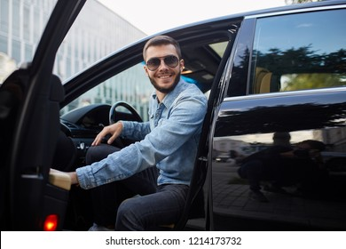 cheerful young brutal man looking at the camer while sitting in the car. close up photo.
