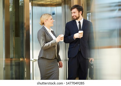 Cheerful young business colleagues in formalwear carrying coffee cups and getting out of elevator