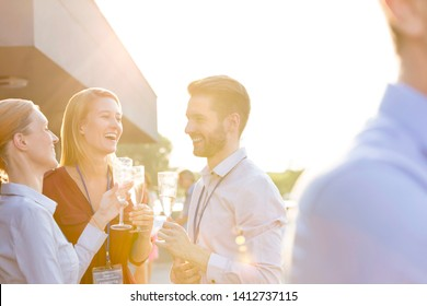 Cheerful young business colleagues talking while standing at rooftop party
