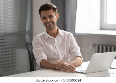 Cheerful young business man laughing sitting at work desk, happy male professional smiling looking away having fun at workplace with laptop, worker express positivity enjoy funny moments in office
