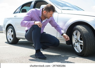 Cheerful young businessman has problems with the wheel of his car. He is kneeing and looking at it with seriousness