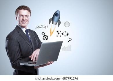 Cheerful young businessman holding laptop with abstract space ship and business chart hologram on gray background. Startup and marketing concept