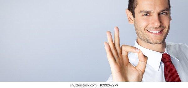 Cheerful young businessman with okay gesture, with blank copyspace area for text or slogan, against grey background