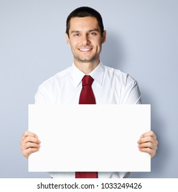 Cheerful young businessman showing blank signboard, against grey background