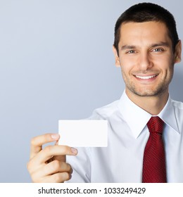 Cheerful young businessman showing blank business or plastic credit card, with copyspace area for text or slogan, against grey background