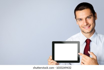 Cheerful young businessman showing blank no-name tablet pc monitor, against grey background, with copyspace area