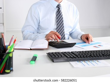 Cheerful young businessman sitting at the table with laptop and stretching in the office.